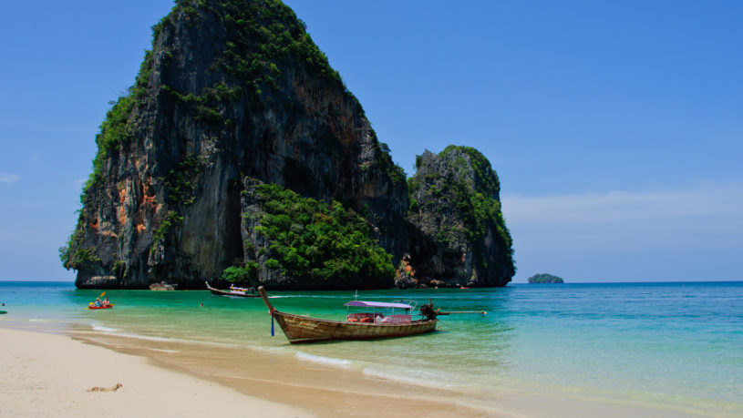 A boat sits at anchor in front of one of the famous karsts (rock formations) near Phra Nang Beach in Krabi, Thailand.